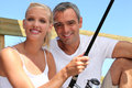 Couple fishing whilst on a vacation abroad Royalty Free Stock Photography
