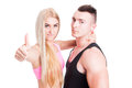 Couple of fitness instructors showing like gesture or thumbs up with confidence to the camera on white studio background Royalty Free Stock Images