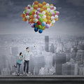 Couple flying with colorful balloons asian young over the cityscape Stock Photo