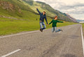 Couple flying road young happy caucasian men and woman having fun and along asphalt among beautiful mountain landscape altai Royalty Free Stock Photo