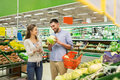 Couple with food basket shopping at grocery store Royalty Free Stock Photo