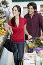 Couple food shopping in supermarket smiling young with list Royalty Free Stock Photo