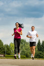 Couple friends running a race in park playful Stock Photography