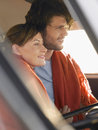 Couple in front seat of campervan loving young wrapped blanket Royalty Free Stock Images