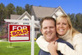 Couple in front of sold real estate sign and house happy hugging Royalty Free Stock Image