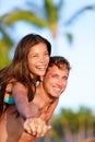 Couple fun on beach man giving piggyback ride to girlfriend beautiful interracial in love asian woman caucasian Royalty Free Stock Photo