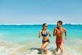 Couple Fun On Beach. Romantic People In Love Running At Sea Royalty Free Stock Photo