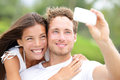 Couple fun taking self portrait picture photos with mobile smart phone or pocket camera outdoors happy multiracial young in Royalty Free Stock Image