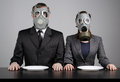 Couple at gas masks on a gray background Stock Photos