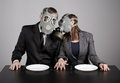 Couple at gas masks on a gray background Royalty Free Stock Photo