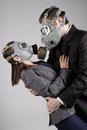Couple at gas masks on a gray background Royalty Free Stock Photography