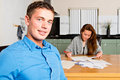 Couple getting their personal finance in order young men sitting at the kitchen table similng at the camera as she just finished Stock Image