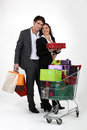 Couple with gifts cart full of Royalty Free Stock Photo