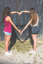 Couple of girls making an heart shaped shadow with arms they are two wearing summer clothes outdoor they are joining their Royalty Free Stock Images