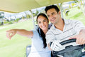 Couple at the golf course happy driving a cart Stock Images