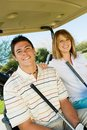 Couple of golfers riding in golf cart Royalty Free Stock Photo