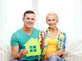 Couple with green house and keys in new home moving concept smiling Royalty Free Stock Photos