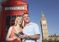 Couple with guidebook against london phone booth and big ben tow middle aged tower Stock Images
