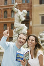 Couple with guidebook looking at monuments young in rome Stock Photo
