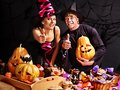 Couple on halloween party sitting at trick or treat table Royalty Free Stock Image