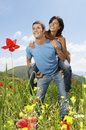 Couple with hand on knee in poppy field young men giving piggyback ride to women while looking away at Royalty Free Stock Image