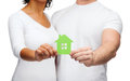 Couple hands holding green house real estate family and eco concept closeup picture of Stock Photography