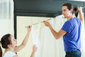 Couple hanging curtains at window Royalty Free Stock Photo