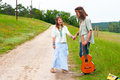 Couple happy hippie on the road hitchhiker in love with guitar Royalty Free Stock Images