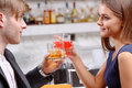 Couple has a drink in the bar toasting for love close up of young attractive holding glasses with drinks with counter on Stock Image