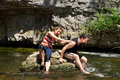 Couple has fun on a rock in the water adult Stock Image