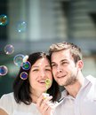 Couple have fun with bubble blower young great time together outside in street Royalty Free Stock Photo