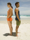 Couple having an argument on the beach stood back to back Royalty Free Stock Image