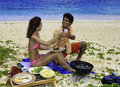 Couple having a beach barbecue Royalty Free Stock Photography