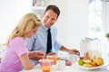 Couple having breakfast before husband leaves for work sitting in kitchen eating cereal Stock Image