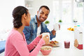 Couple having breakfast in kitchen together holding hot drink whilst smiling at each other Stock Photography
