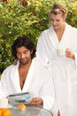 Couple having breakfast outside in matching robes Royalty Free Stock Images