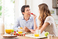 Couple having breakfast portrait of happy young woman feeding strawberry to man Royalty Free Stock Images