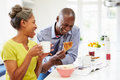 Couple Having Breakfast And Reading Magazine In Kitchen Royalty Free Stock Photo