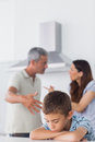 Couple having dispute in front of their sad son sitting kitchen at home Stock Images