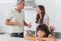 Couple having dispute in front of their unhappy daughter unsmiling sitting kitchen at home Royalty Free Stock Photos