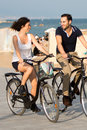 Couple having fon on bikes two persons cycling a city beach Royalty Free Stock Images