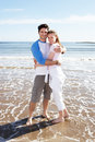 Couple having fun on beach holiday smiling to camera Royalty Free Stock Image