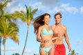 Couple having fun on beach vacation travel laughing happy running together playful and joyful woman in bikini and men in swimwear Stock Photos