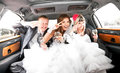 Couple having fun with friends in limousine newly married Stock Images