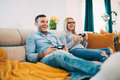 Couple having fun and laughing while playing video games in modern living room Royalty Free Stock Photo