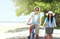 Couple having fun riding bicycle at the beach carefree and smiling Stock Photos