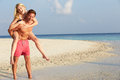 Couple having fun on tropical beach holiday smiling to camera Royalty Free Stock Image