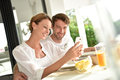 Couple having fun using smartphone and eating breakfast Royalty Free Stock Photo