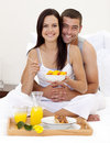 Couple having nutritive breakfast in bed Stock Photography
