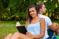 Couple having picnic. Pretty girl reads. Man is using tablet Royalty Free Stock Photo